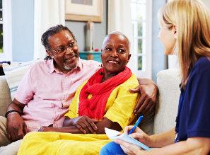 caregiver talking to elderly couple