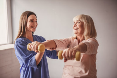 young caregiver helping old lady doing excercises