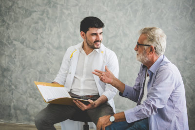 old man and male speech therapist having session