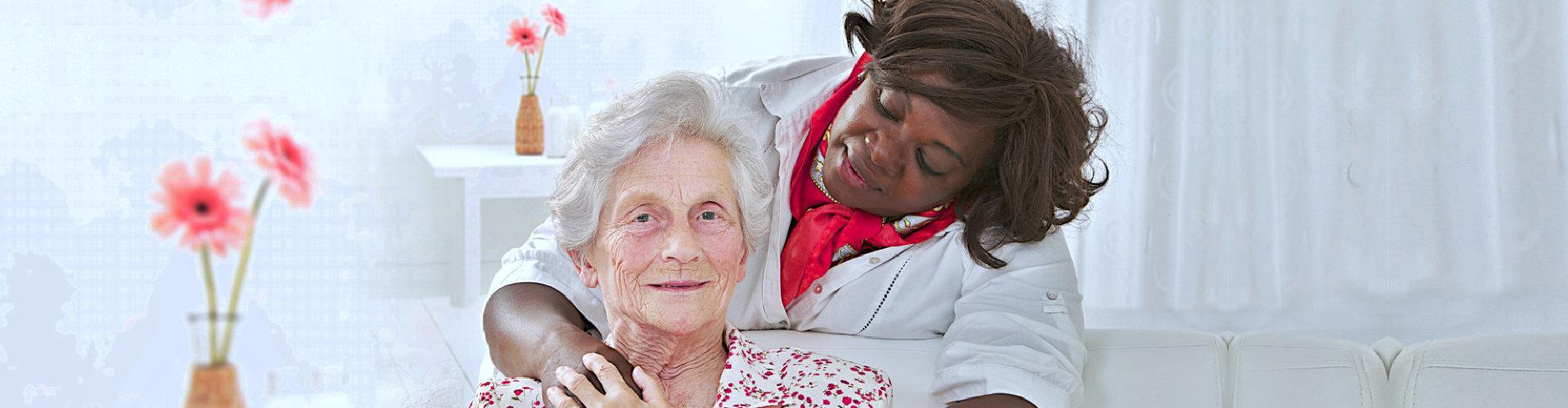 happy senior woman with friendly lady caregiver